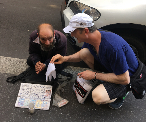 Dr. Brian handing out new socks to a homeless person in Milan, Italy.